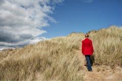 Γυναίκα που περπατά στους αμμόλοφους άμμου Στοκ εικόνα με δικαίωμα ελεύθερης χρήσης