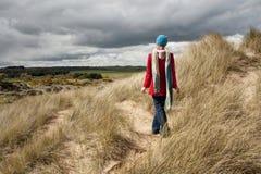 Γυναίκα που περπατά στους αμμόλοφους άμμου Στοκ Φωτογραφίες