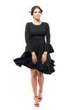 Γυναίκα που περπατά το μπροστινό μαύρο πετώντας φόρεμα εκμετάλλευσης με το φυσώντας αέρα στην τρίχα και τα ενδύματα Στοκ Φωτογραφία