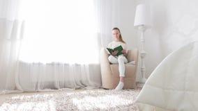 Γυναίκα που πηγαίνει να διαβάσει στην κρεβατοκάμαρά της απόθεμα βίντεο