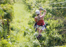 Γυναίκα που πηγαίνει σε μια περιπέτεια zipline ζουγκλών Στοκ Εικόνες