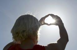 Γυναίκα που πιάνει τον ήλιο Στοκ Εικόνες