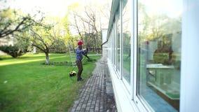 Γυναίκα που πλένει το συντηρητικό παράθυρο με την προβολή ύδατος που απεικονίζει στο γυαλί εστίαση απόθεμα βίντεο
