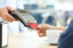 Γυναίκα που πληρώνει με τον αναγνώστη πιστωτικών καρτών σε έναν φραγμό Στοκ εικόνες με δικαίωμα ελεύθερης χρήσης