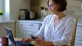Γυναίκα που πληρώνει on-line με την πιστωτική κάρτα και το σημειωματάριό της φιλμ μικρού μήκους
