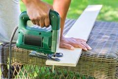 Γυναίκα που πριονίζει την ξύλινη σανίδα με το ηλεκτρικό πριόνι Στοκ φωτογραφία με δικαίωμα ελεύθερης χρήσης