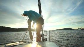 Γυναίκα που προετοιμάζει τα σχοινιά στο τόξο sailboat στην αδριατική θάλασσα στην Κροατία απόθεμα βίντεο