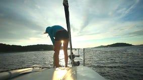 Γυναίκα που προετοιμάζει τα σχοινιά στο τόξο sailboat στην αδριατική θάλασσα στην Κροατία φιλμ μικρού μήκους