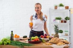 Γυναίκα που προετοιμάζει το γεύμα σε μια κουζίνα, πίνοντας το μαγείρεμα έννοιας χυμού, μαγειρικός, υγιής τρόπος ζωής στοκ εικόνες
