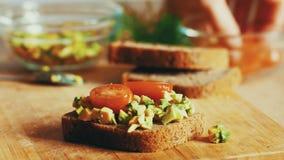 Γυναίκα που προετοιμάζει το σάντουιτς με το αβοκάντο, την ντομάτα και τις ελιές 4K στενός επάνω βαθμολογημένος απόθεμα βίντεο