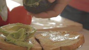 Γυναίκα που προετοιμάζει το υγιές πρόγευμα με το αβοκάντο στο ψημένες ψωμί, τα αυγά και την ντομάτα απόθεμα βίντεο