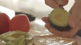 Γυναίκα που προετοιμάζει το υγιές πρόγευμα με το αβοκάντο στο ψημένες ψωμί, τα αυγά και την ντομάτα φιλμ μικρού μήκους