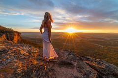 Γυναίκα που προσέχει τα πανευτυχή sunsets από τις κρυμμένες προεξοχές απότομων βράχων στοκ εικόνες