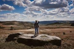 Γυναίκα που προσέχει την άποψη στους βράχους του Derbyshire στοκ φωτογραφία