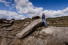 Γυναίκα που προσέχει την άποψη στους βράχους του Derbyshire στοκ εικόνες