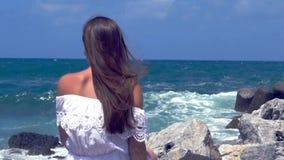Γυναίκα που προσέχει τη θάλασσα με τη συντριβή κυμάτων σε αργή κίνηση απόθεμα βίντεο