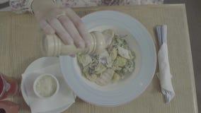 Γυναίκα που προσθέτει στο σπίτι το άλας στο γεύμα Αλατισμένος δονητής, αλάτι, τρόφιμα Το πιάτο των τροφίμων, η άποψη από την κορυ φιλμ μικρού μήκους