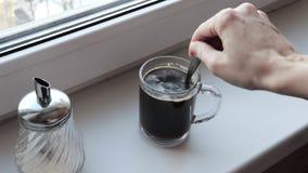 Γυναίκα που προσθέτει τη ζάχαρη σε έναν μαύρο καφέ στο διαφανές σαφές φλυτζάνι γυαλιού το πρωί απόθεμα βίντεο