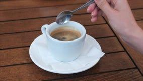Γυναίκα που προσθέτει τη ζάχαρη στο μαύρο καφέ απόθεμα βίντεο