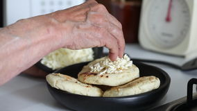 Γυναίκα που προσθέτει το τεμαχισμένο τυρί σε ένα ψημένο arepa φιλμ μικρού μήκους