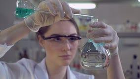Γυναίκα που προσθέτει το υγρό στο βολβό γυαλιού απόθεμα βίντεο