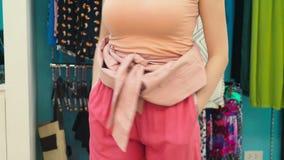 Γυναίκα που προσπαθεί στα ενδύματα στο κατάστημα ιματισμού φιλμ μικρού μήκους
