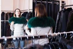 Γυναίκα που προσπαθεί στη γούνα neckpiece στο κατάστημα υφασμάτων women's στοκ φωτογραφίες