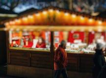 Γυναίκα που πωλεί τα μικροσκοπικά σπίτια στην αγορά Χριστουγέννων στοκ εικόνες