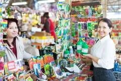 Γυναίκα που πωλεί το υγρό λίπασμα στον ώριμο αγοραστή στοκ εικόνες