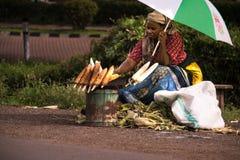 Γυναίκα που πωλεί το ψημένο καλαμπόκι στην άκρη του δρόμου της Τανζανίας Στοκ Φωτογραφίες