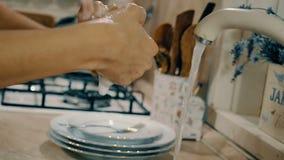 Γυναίκα που πλένει τα χέρια της με το σαπούνι στην κουζίνα Άποψη κινηματογραφήσεων σε πρώτο πλάνο με τη δευτερεύουσα κίνηση καμερ φιλμ μικρού μήκους