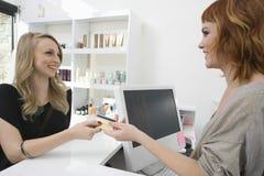 Γυναίκα που πληρώνει μέσω της πιστωτικής κάρτας στο κομμωτήριο Στοκ Εικόνες