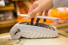 Γυναίκα που πληρώνει με την τεχνολογία nfc στο κινητό τηλέφωνο, που ψωνίζει, supe Στοκ εικόνες με δικαίωμα ελεύθερης χρήσης