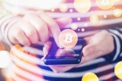 Γυναίκα που πληρώνει με Bitcoins πέρα από το κινητό smartphone Στοκ Εικόνες