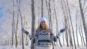 Γυναίκα που ρίχνει το χιόνι επάνω και που στέκεται στις χιονοπτώσεις το χειμώνα μια μυθική ημέρα απόθεμα βίντεο