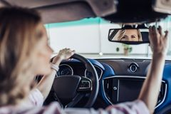 Γυναίκα που ρυθμίζει τον οπισθοσκόπο καθρέφτη στο αυτοκίνητο στοκ φωτογραφίες