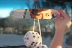 Γυναίκα που ρυθμίζει τον οπισθοσκόπο καθρέφτη Στοκ Φωτογραφία