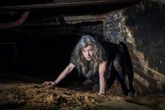 Γυναίκα που σέρνεται στο εγκαταλελειμμένο κτήριο Στοκ εικόνα με δικαίωμα ελεύθερης χρήσης