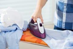 Γυναίκα που σιδερώνει το αρσενικό πουκάμισο Στοκ Εικόνες