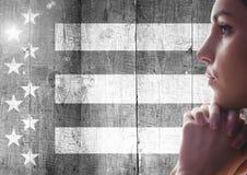 Γυναίκα που σκέφτεται ενάντια στη γραπτή αμερικανική σημαία Στοκ εικόνα με δικαίωμα ελεύθερης χρήσης