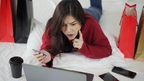 Γυναίκα που σκέφτεται και που χρησιμοποιεί το φορητό προσωπικό υπολογιστή για on-line να ψωνίσει με την πιστωτική κάρτα στο κρεβά απόθεμα βίντεο