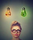 Γυναίκα που σκέφτεται να εξετάσει επάνω το άχρηστο φαγητό και τα πράσινα λαχανικά που διαμορφώνονται ως λάμπα φωτός επάνω από το  Στοκ εικόνα με δικαίωμα ελεύθερης χρήσης