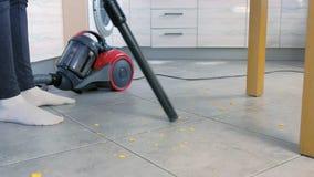 Γυναίκα που σκουπίζει το πάτωμα κουζινών με το γκρίζο κεραμίδι χωρίς βούρτσα, μόνο σωλήνας της ηλεκτρικής σκούπας με ηλεκτρική σκ φιλμ μικρού μήκους