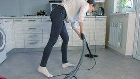 Γυναίκα που σκουπίζει το πάτωμα κουζινών με ηλεκτρική σκούπα Τακτοποιεί τις νιφάδες καλαμποκιού που διασκορπίζονται στο γκρίζο κε φιλμ μικρού μήκους