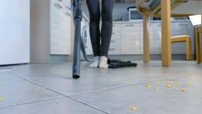 Γυναίκα που σκουπίζει το πάτωμα κουζινών χωρίς βούρτσα με ηλεκτρική σκούπα Κινηματογράφηση σε πρώτο πλάνο ποδιών απόθεμα βίντεο