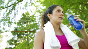 Γυναίκα που σκουπίζει το brow και το πόσιμο νερό της μετά από το workout στο πάρκο φιλμ μικρού μήκους