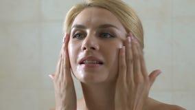 Γυναίκα που στάζει το καλλυντικό πετρέλαιο στο πρόσωπό της στο λουτρό, χρήσιμα υγιή οξέα απόθεμα βίντεο