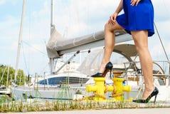 Γυναίκα που στέκεται ένα πόδι στη μαρίνα bitt Στοκ Φωτογραφίες