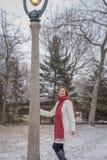 Γυναίκα που στέκεται δίπλα στην περίκομψη μετα τοποθέτηση λαμπτήρων για τη φωτογραφία στο χιόνι Στοκ φωτογραφία με δικαίωμα ελεύθερης χρήσης