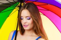 Γυναίκα που στέκεται κάτω από τη ζωηρόχρωμη ομπρέλα ουράνιων τόξων Στοκ Φωτογραφία
